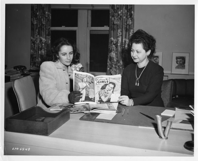 "Elizabeth Taylor and Frances Ullmann look at ""Calling All Girls"" magazine with Taylor on the cover, seated indoors"