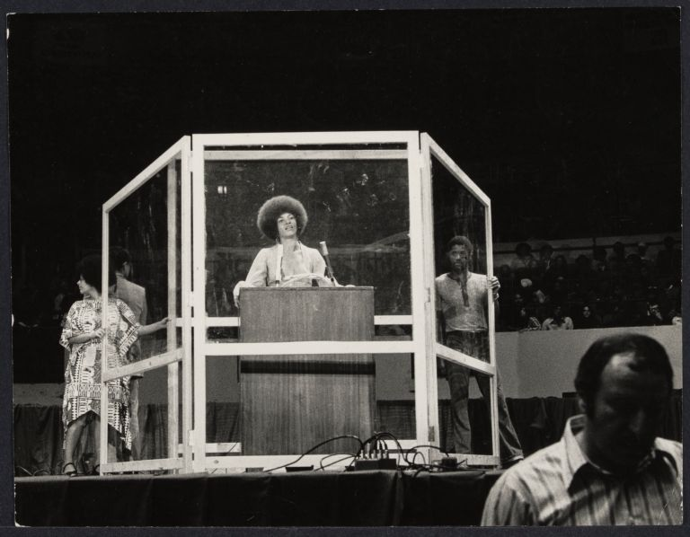 """Bullet proof cage surrounds Angela Davis as she performs in """"Night with Angela Davis"""" at Madison Square Garden"""