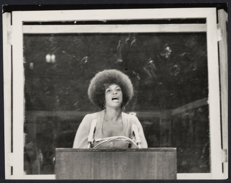 Angela Davis speaking from behind bulletproof glass at a lecturn.
