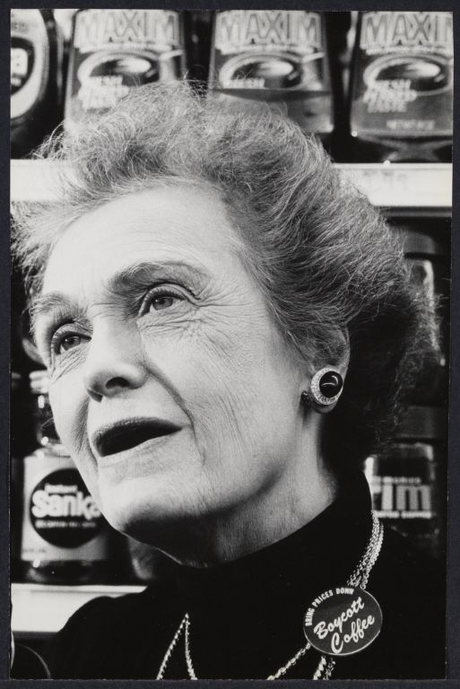 "A portrait of Elinor Guggenheimer, photographed in 1976. She is mid-speech, and wearing a pin that reads ""boycott coffee."""