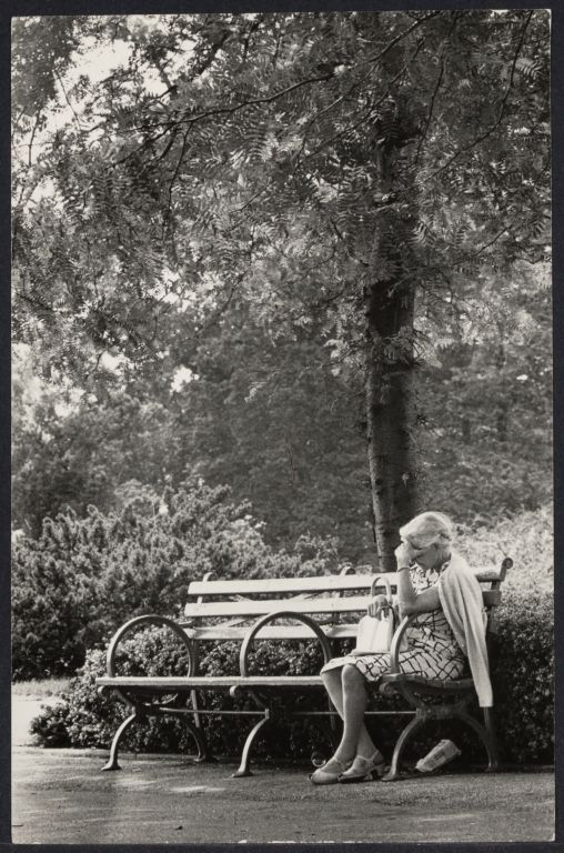 Older woman on bench, head in her hands.