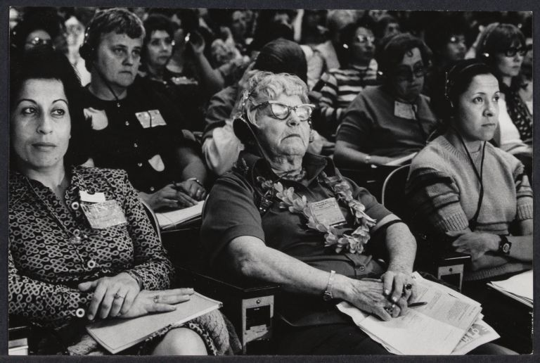 International women attend Non-Governmental Organization conference, seated in rows.