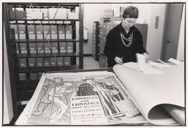 Eva Moseley in the Schlesinger Library with suffrage posters.