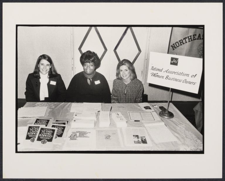 """Three women in business atire sitting at a table with a sign that reads """"National Association of Women Business Owners."""""""