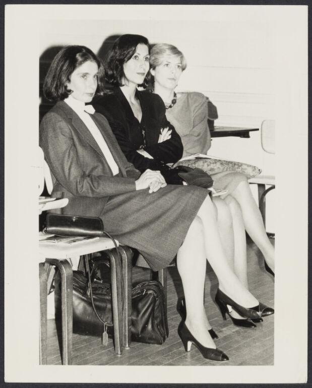 Three women in business attire sitting in a row.