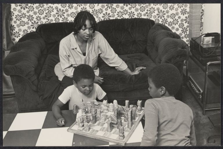Mother teaching sons to play chess