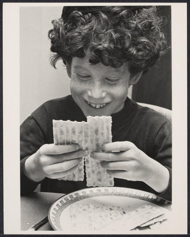 Boy breaking matzo at Passover