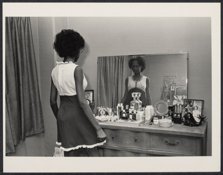Teenager dresses for party, reflected in a mirror.