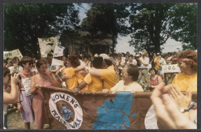 Opening day celebrations at the Women's Encampment for a Future of Peace and Justice. Women holding a brown and blue banner, wearing yellow shirts, some also carrying signs.