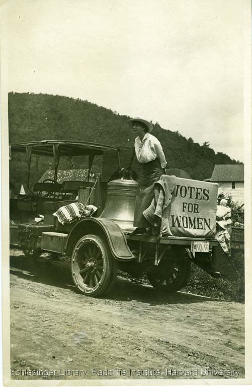"""Louise Hall speaking from the back of the vehicle holding the Liberty Bell and a """"Votes for Women"""" banner during a suffrage campaign stop in Pennsylvania, 1915."""