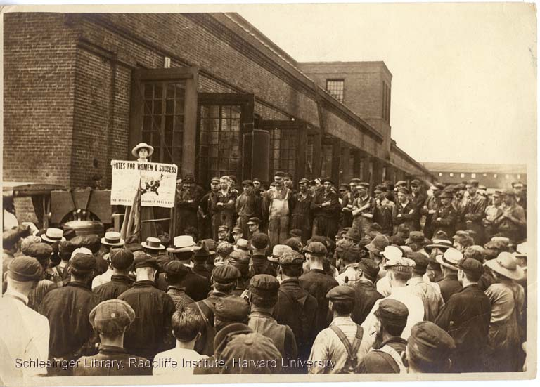 Louise Hall speaking outdoors to a crowd of men, perhaps workers from area businesses, during a stop on the Pennsylvania suffrage campaign, 1915.
