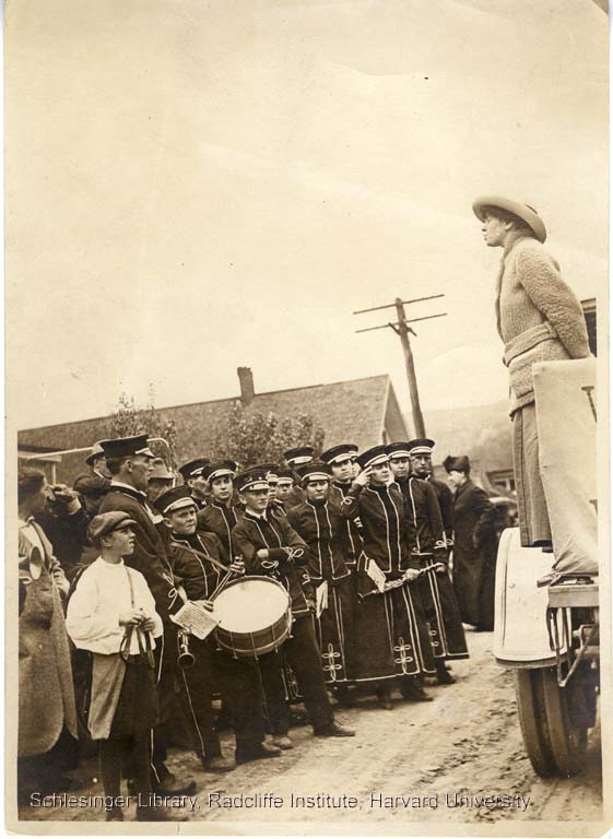Lousie Hall speaking to a crowd from the platform of a truck, members of a local band are in the front, 1915.