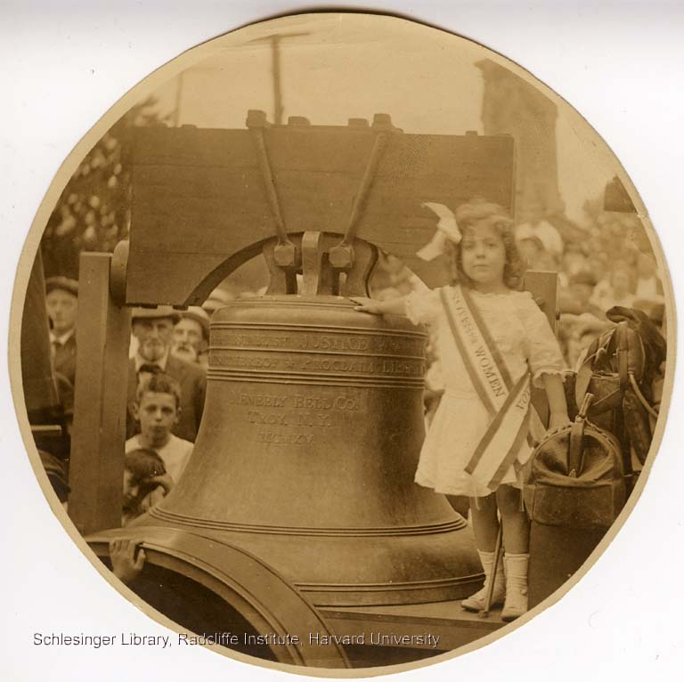 "Informal portrait of a young girl standing with the ""Justice Bell,"" a replica of the Liberty Bell, during a suffrage rally in Pennsylvania."