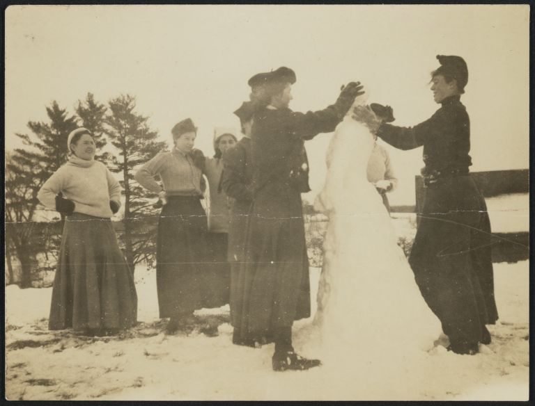 Members of The Club building a snowman