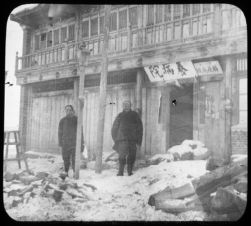 "Dr. Ku and assistant in front of ""old style"" Chinese plague hospital, Fuchiatien"