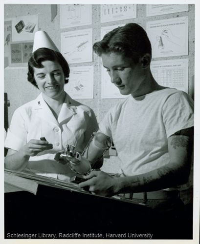 Nurse with a patient testing a prosthetic arm