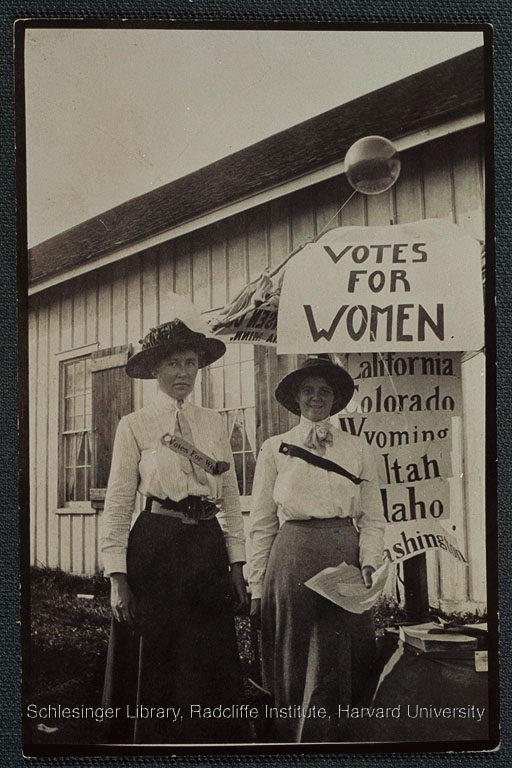 "Katharine Dummer and Constance Perry taken while campaigning for suffrage at the Walworth County Fair with a ""Votes for Women"" sign."