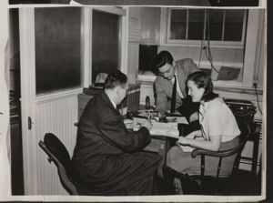 News Office photographer, Mr. William Tauberg, discusses pictures with Doug Brown and Mrs. Thompson [photograph], Digital Object